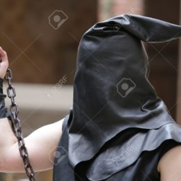 executioner with black hood on his head and the chain with the sentenced to death